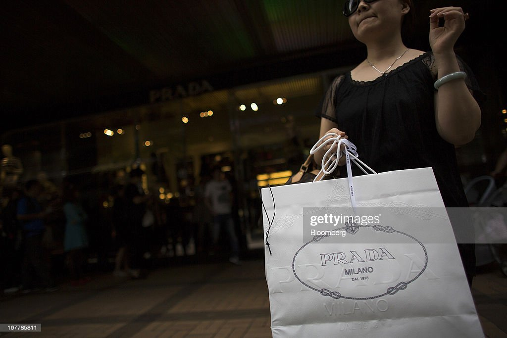 A woman holds a Prada SpA branded shopping bag as customers wait in line to enter a Prada SpA store in the Tsim Sha Tsui area of Hong Kong, China, on Tuesday, April 30, 2013. Financial Secretary John Tsang on Feb. 27 projected annual growth of 1.5 percent to 3.5 percent this year following 2012's 1.4 percent, the weakest rate since 2009 as Europe's sovereign debt crisis sapped global demand. Photographer: Lam Yik Fei/Bloomberg via Getty Images