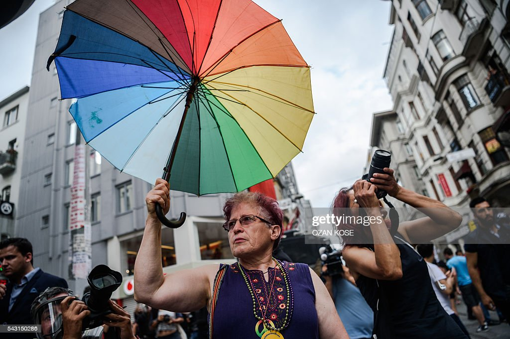 A woman holds a rainbow umbrella during a rally staged by the LGBT community on Istiklal avenue in Istanbul on June 26, 2016. Riot police fired tear gas and rubber bullets to disperse protesters defying a ban on the city's Gay Pride parade. Authorities in Turkey's biggest city had banned the annual parade earlier this month citing security reasons, sparking anger from gay rights activists. KOSE