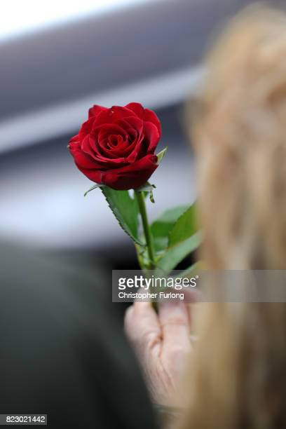 A woman holds a red rose outside the funeral of Manchester Attack victim Saffie Roussos arrives at Manchester Cathedral on July 26 2017 in Manchester...