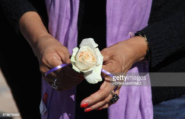 A woman holds a rose during a protest on the eve of the International Day for the Elimination of Violence Against Women on November 24 in Juarez...