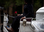 A woman holds a rose while riding in a horse drawn carriage carrying the casket of Philando Castile after his funeral at the Cathedral of St Paul on...