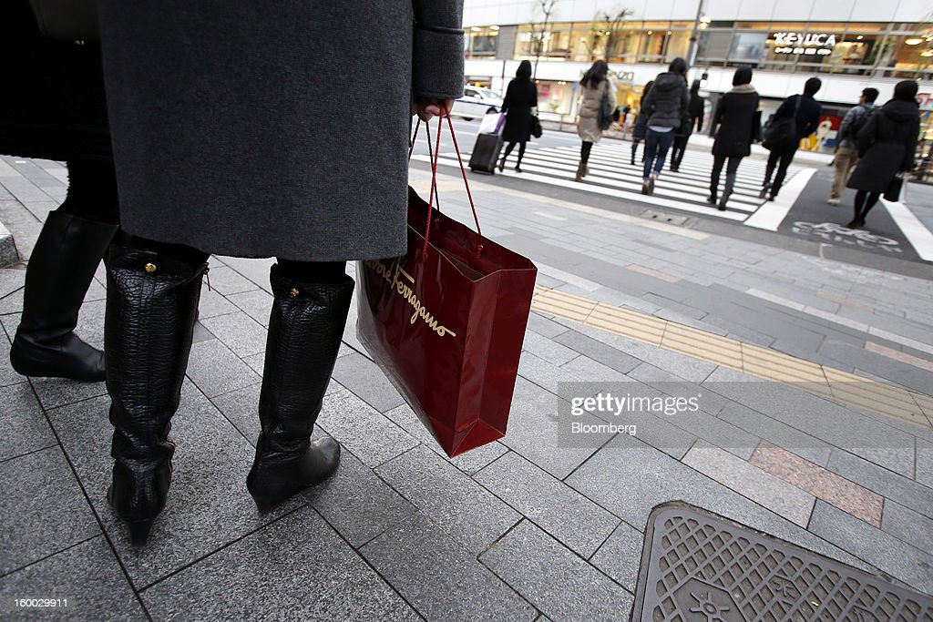 A woman holds a Salvatore Ferragamo SpA shopping bag in the Ginza district of Tokyo, Japan, on Friday, Jan. 25, 2013. Japan's consumer prices fell for the seventh time in eight months, underscoring the risk that the central bank may struggle to reach a 2 percent inflation target unless it implements new easing measures earlier than planned. Photographer: Kiyoshi Ota/Bloomberg via Getty Images