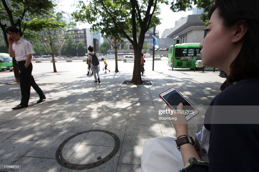 A woman holds a Samsung Electronics Co. smartphone near a bus stop in Gwanghwamun Square in Seoul, South Korea, on Wednesday, July 3, 2013. Samsung Electronics lost $25.3 billion in market capitalization last month, more than the value of competitor Sony Corp., as sales of its flagship Galaxy S4 smartphone fell short of investor expectations. Photographer: Woohae Cho/Bloomberg via Getty Images