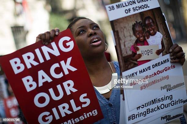 A woman holds a sign as other protesters gather outside Nigeria House to mark the one year anniversary since a group of Nigerian schoolgirls were...