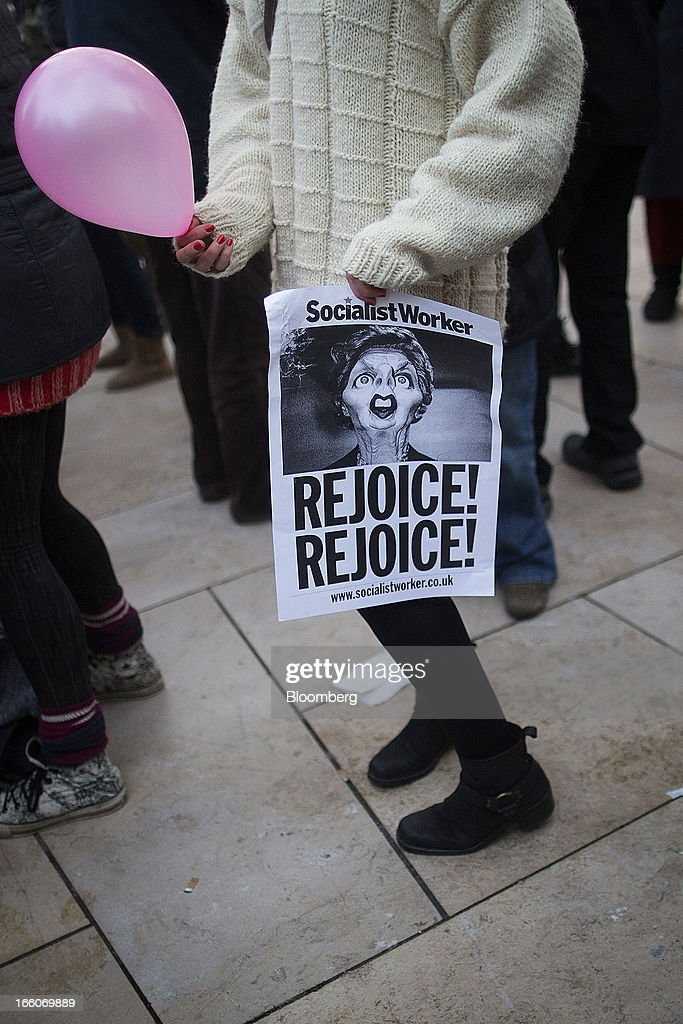 A woman holds a sign as people gather to mark the death of former premier Margaret Thatcher in the Brixton district of London, U.K., on Monday, April 8, 2013. Thatcher, the former U.K. prime minister who helped end the Cold War and was known as the 'Iron Lady' for her uncompromising style, died today. She was 87. Photographer: Simon Dawson/Bloomberg via Getty Images