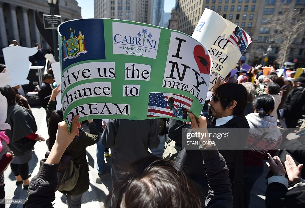 A woman holds a sign as she joins a coalition of New York area groups during a rally to call on Congress to move on immigration reform in Foley Square April 10, 2014 in New York. AFP PHOTO/Stan HONDA