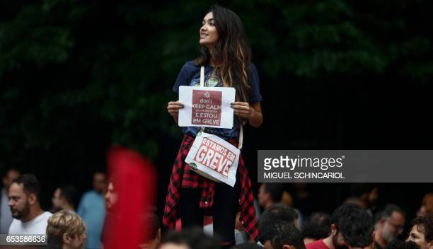 A woman holds a sign as she takes part of a protest during a national strike against the government's social welfare reform bill which seeks to...