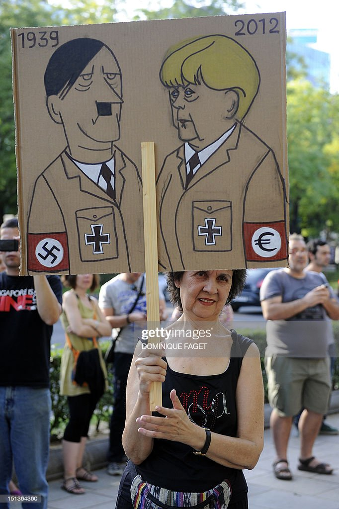 A woman holds a sign comparing Adolph Hitler to German Chancellor Angela Merkel during a demonstration against her official visit to Spain, in central Madrid on September 6, 2012. Merkel is in Spain for talks with conservative Spanish President Mariano Rajoy.