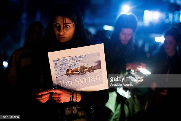 A woman holds a sign during a candle light vigil in honour of Syrian refugee Aylan Kurdi and in protest against the Australian government's position...