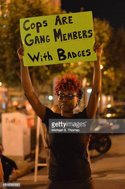 A woman holds a sign during a protest action through the Central West End of St Louis Missouri on August 20 2015 After a night of unrest sparked by a...