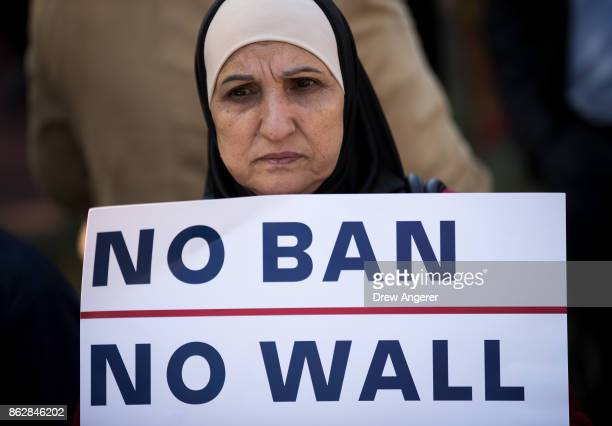 A woman holds a sign during a protest against the Trump administration's proposed travel ban October 18 2017 in Washington DC Early Wednesday morning...
