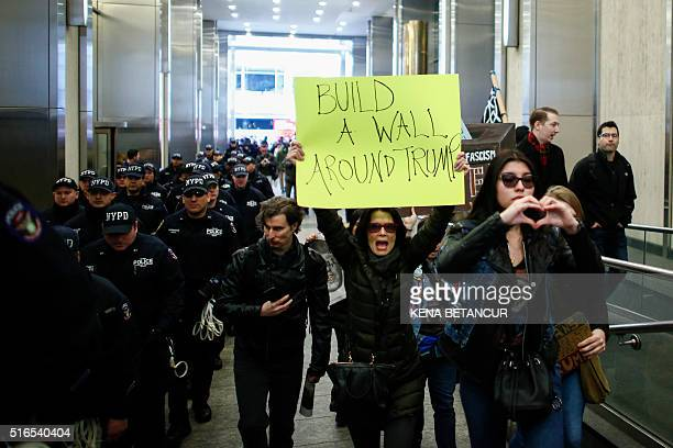 TOPSHOT A woman holds a sign during a protest rally against Republican presidential frontrunner Donald Trump in New York on March 192016 / AFP / KENA...