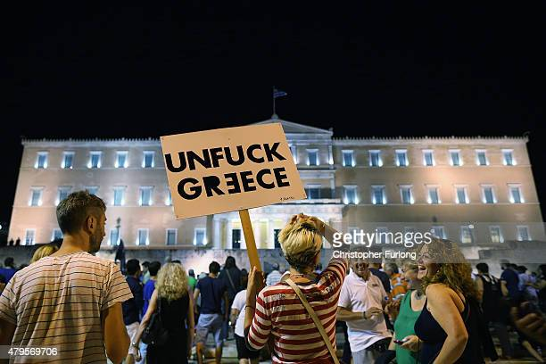 A woman holds a sign in front of the Greek parliament as early opinion polls predict a win for the Oxi or No campaign in the Greek austerity...