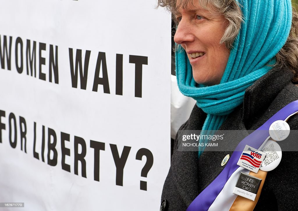 A woman holds a sign in front of the White House in Washington on March 2, 2013 during an event to commemorate the 100th anniversary of the Suffrage March. On March 3, 1913, on the eve of President Woodrow Wilson's inauguration, masses of suffragists from many states filled the streets around the US Capitol, White House, and Treasury Building. In 1920, the 72-year struggle ended with the ratification of the 19th Amendment, the 'Susan B. Anthony' Amendment, granting women the vote. AFP PHOTO/Nicholas KAMM