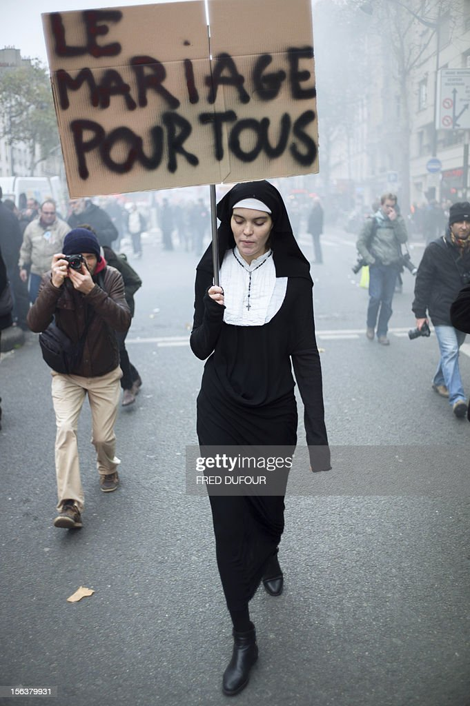 A woman holds a sign 'marriage for all' as she attends a demonstration called by unions, as part an European day of protest against austerity, on November 14, 2012 in Paris. General strikes in Spain and Portugal will spearhead the day of action called by European unions and joined by activists as anger over governments' tight-fisted policies boils over.