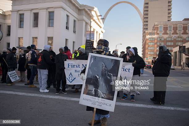 TOPSHOT A woman holds a sign of a portrait of Dr Martin Luther King Jr prior to a march outside the Old Courthouse on January 18 2016 in St Louis...
