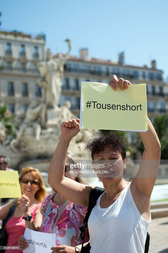 A woman holds a sign reading 'All in shorts', during the 'Marche des Shorts' (The March of the Shorts) to show support to a young woman who was attacked in a bus because she wearing shorts, in Toulon, southeastern France, on June 25, 2016. / AFP / BERTRAND