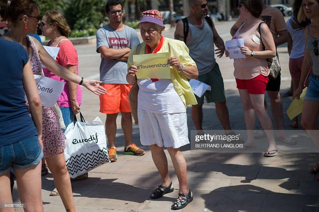 A woman holds a sign reading 'All in shorts' during the 'Marche des Shorts' (The March of the Shorts) to show support to a young woman who was attacked in a bus because she wearing shorts, in Toulon, southeastern France, on June 25, 2016. / AFP / BERTRAND