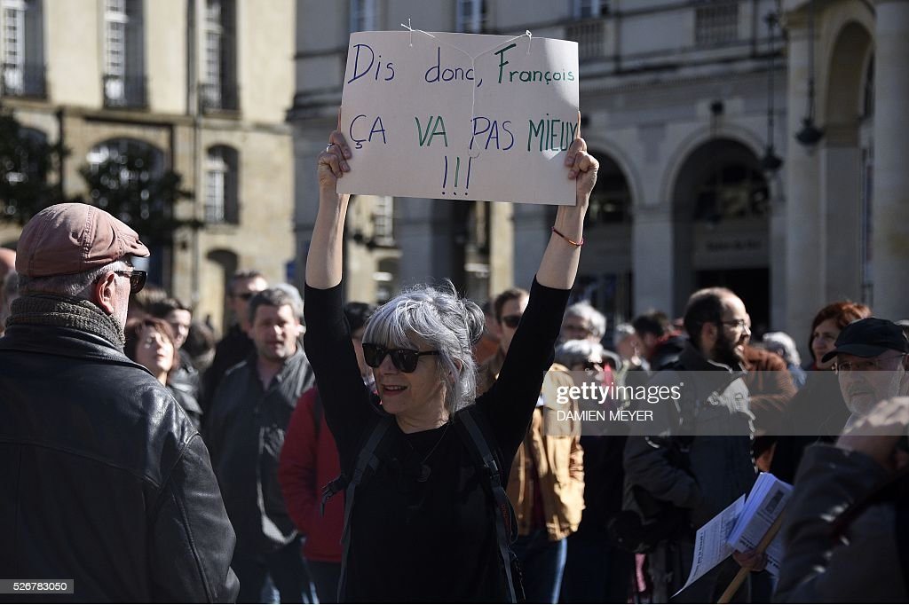 A woman holds a sign reading 'By the way, Francois, is everything OK?' during a May Day rally in Rennes, western France, on May 1, 2016. / AFP / DAMIEN