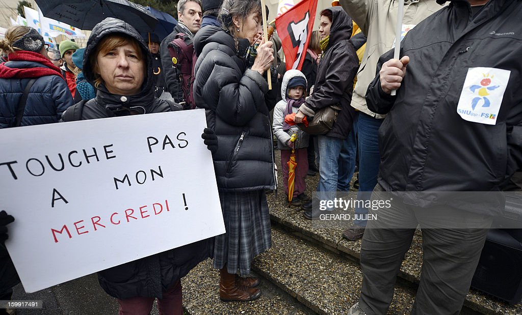 A woman holds a sign reading 'Don't touch my Wednesday' as she and other French teachers take part in a nationwide strike and protest action against a proposed reform to increase the class time of primary school students, on January 23, 2013, in Marseille, southern France. The strike and rally was called by French educational trade unions to protest a reform proposition by France's Education Minister, planned for the 2013-2014 schoolyear, which foresees an increase of class time in primary schools to 4.5 days a week and would affect both students and teachers.