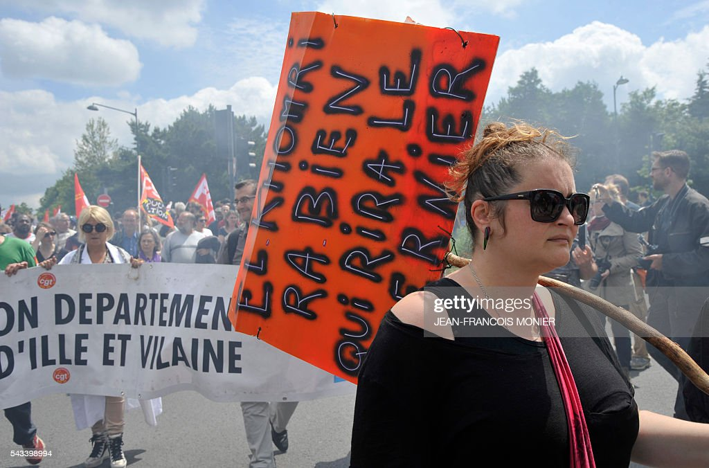 A woman holds a sign reading 'El Khomri, who laughs last laughs best' during a demonstration against controversial labour reforms on June 28, 2016 in Rennes. Unions have called repeated strikes and marches in opposition to the law, which seeks to bring down France's intractable 10-percent unemployment rate by making it easier to hire and fire workers.