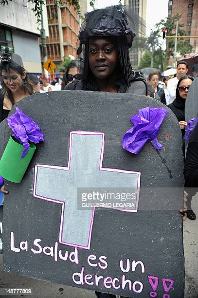A woman holds a sign reading 'Health is a right' during a protest against the health care system in Bogota Colombia on July 19 demanding the...