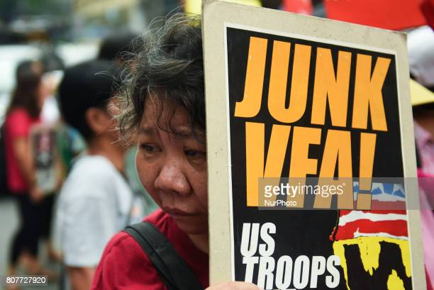 A woman holds a sign reading Junk VFA as militant groups attempt to march towards the US Embassy in Manila on Filipino American friendship day 04...