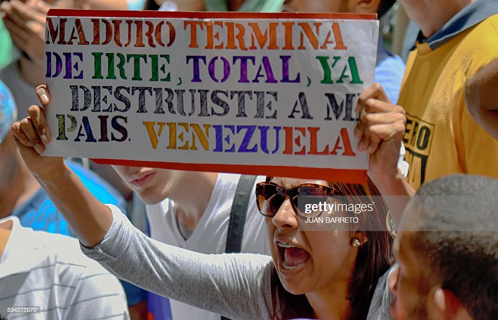 A woman holds a sign reading 'Maduro, go for once, you have already destroyed mi country, Venezuela' during a protest outside the Supreme Tribunal of Justice (TSJ) in Caracas on May 25, 2016. Protesters seeking to drive Venezuelan President Maduro from office launched fresh street rallies on Wednesday, a test of their strength in a tense political crisis. / AFP / JUAN
