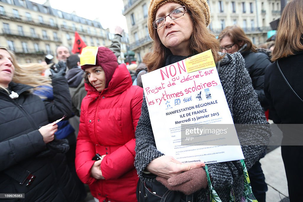 A woman holds a sign reading 'NO to the decree calling for a change in school class hours', on January 23, 2013, in Paris, as he and other teachers take part in a nationwide strike and protest action against a proposed reform to increase the class time of primary school students. The strike and rally was called by French educational trade unions to protest a reform proposition by France's Education Minister, planned for the 2013-2014 schoolyear, which foresees an increase of class time in primary schools to 4.5 days a week and would affect both students and teachers. AFP PHOTO / THOMAS SAMSON