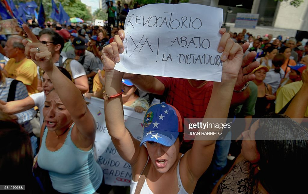 A woman holds a sign reading 'Recall now! Down with the dictatorship' during a protest outside the Supreme Tribunal of Justice (TSJ) in Caracas on May 25, 2016. Protesters seeking to drive Venezuelan President Nicolas Maduro from office launched fresh street rallies on Wednesday, a test of their strength in a tense political crisis. / AFP / JUAN