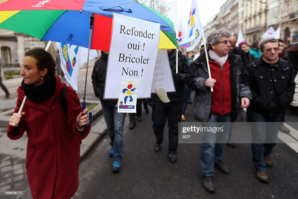 A woman holds a sign reading 'Remaking the school system YES ! Quick fixes NO !', on January 23, 2013, in Paris, as she and other teachers take part in a nationwide strike and protest action against a proposed reform to increase the class time of primary school students. The strike and rally was called by French educational trade unions to protest a reform proposition by France's Education Minister, planned for the 2013-2014 schoolyear, which foresees an increase of class time in primary schools to 4.5 days a week and would affect both students and teachers.