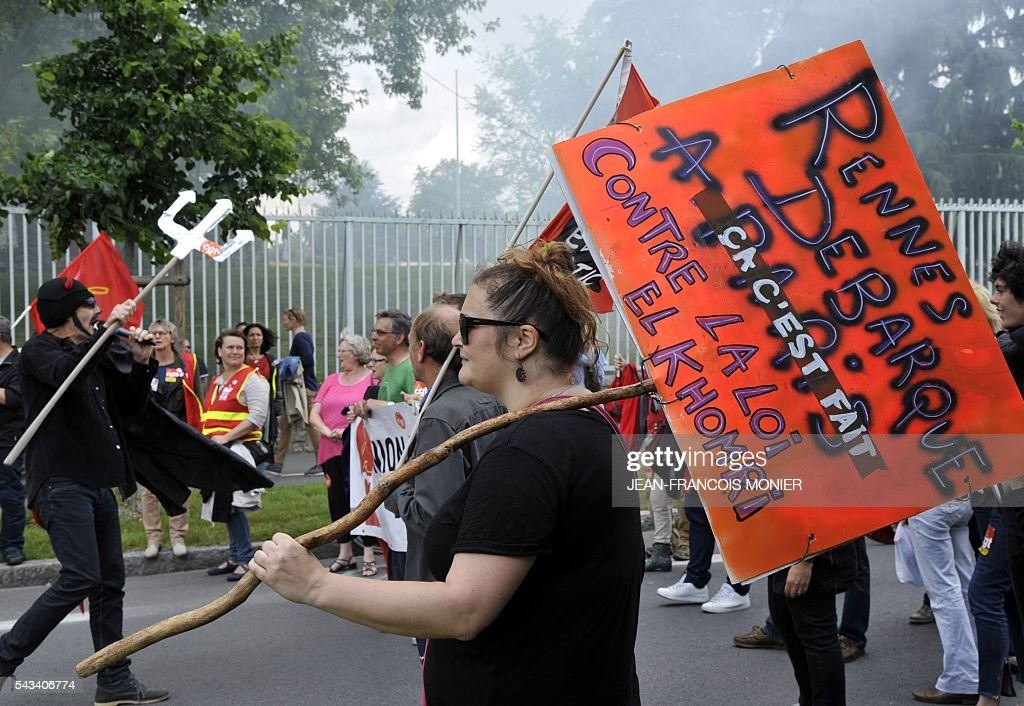 A woman holds a sign reading 'Rennes turns up in Paris - done - against the El Khomri law' during a demonstration against the French controversial labour reforms on June 28, 2016 in Rennes. Unions have called repeated strikes and marches in opposition to the law, which seeks to bring down France's intractable 10-percent unemployment rate by making it easier to hire and fire workers. / AFP / JEAN