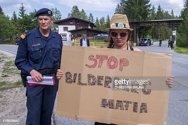 A woman holds a sign reading 'Stop Bilderberg Mafia' in front of a police checkpoint on a road leading to the InteralpenHotel Tirol venue of the...