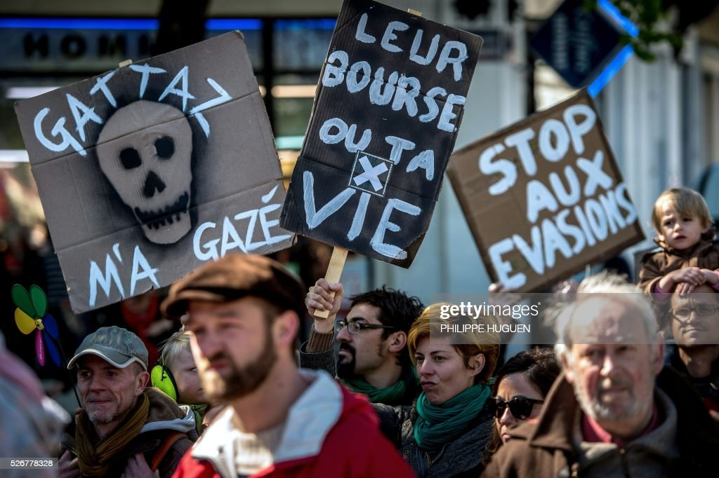 A woman holds a sign reading 'Their stock exchange or your life' as people march in the streets of Lille during a May Day rally on May 1, 2016. / AFP / PHILIPPE