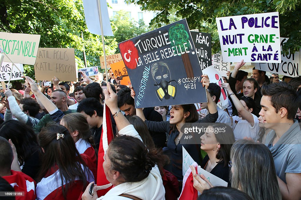 A woman holds a sign reading 'Turkey, the beautiful rebel' as she takes part in a protest in support of people wounded in ongoing demonstrations in Turkey, on June 4, 2013, in Paris. Meanwhile protests continued in Turkey against the ruling party, police brutality, and the destruction of Taksim park in Istanbul for the sake of a development project. Turkey's Islamic-rooted government apologised today to wounded protestors and said it had 'learnt its lesson' after days of mass street demonstrations that have posed the biggest challenge to Prime Minister Recep Tayyip Erdogan's decade in office. What started as an outcry against a local development project has snowballed into widespread anger against what critics say is the government's increasingly conservative and authoritarian agenda. AFP PHOTO / THOMAS SAMSON