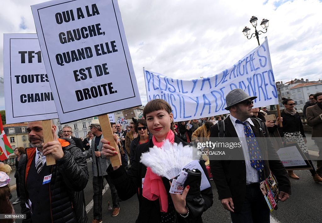 A woman holds a sign reading 'Yes to the left when its right-leaning' as members of the movement 'Bizi !' ('live' in Basque) stage a 'Rich peoples protest' to mark May Day in Bayonne on May 1, 2016. / AFP / IROZ