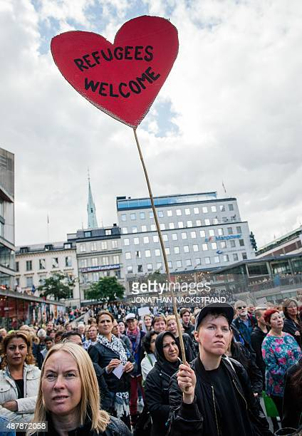A woman holds a sign 'refugees welcome' as she takes part in a demonstration in solidarity with migrants seeking asylum in Europe after fleeing their...