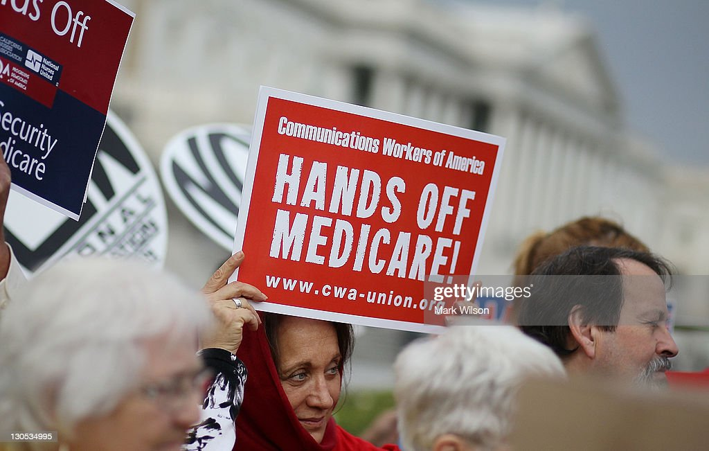 A woman holds a sign that reads 'Hands Off Medicare' during a news conference at the U.S. Capitol October 26, 2011 in Washington, DC. Members of Congress called on the Joint Deficit Reduction Committee to preserve Medicare, Medicaid, and Social Security benefits when making their decision on cutting the deficit.