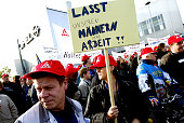A woman holds a sign that reads 'Let Our Men Work' as she joins thouands protesting annouced job cuts outside the local Opel car factory October 19...