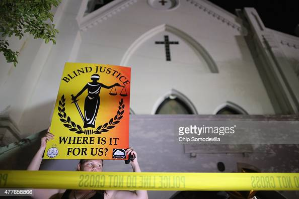 A woman holds a silent vigil for the nine victims of last night's shooting at the historic Emanuel African Methodist Episcopal Church June 18 2015 in...