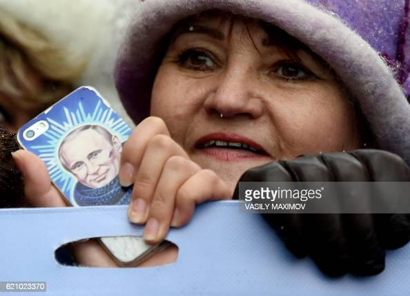 TOPSHOT A woman holds a smartphone bearing an image of Russian President Vladimir Putin as ProKremlin supporters march in central Moscow on November...