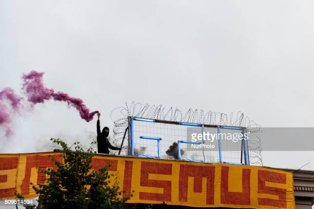 A Woman holds a smoke grenade beside a G20 neon sign on the roof of the autonomous center Rote Flora in the air About 20000 people demonstrated in a...