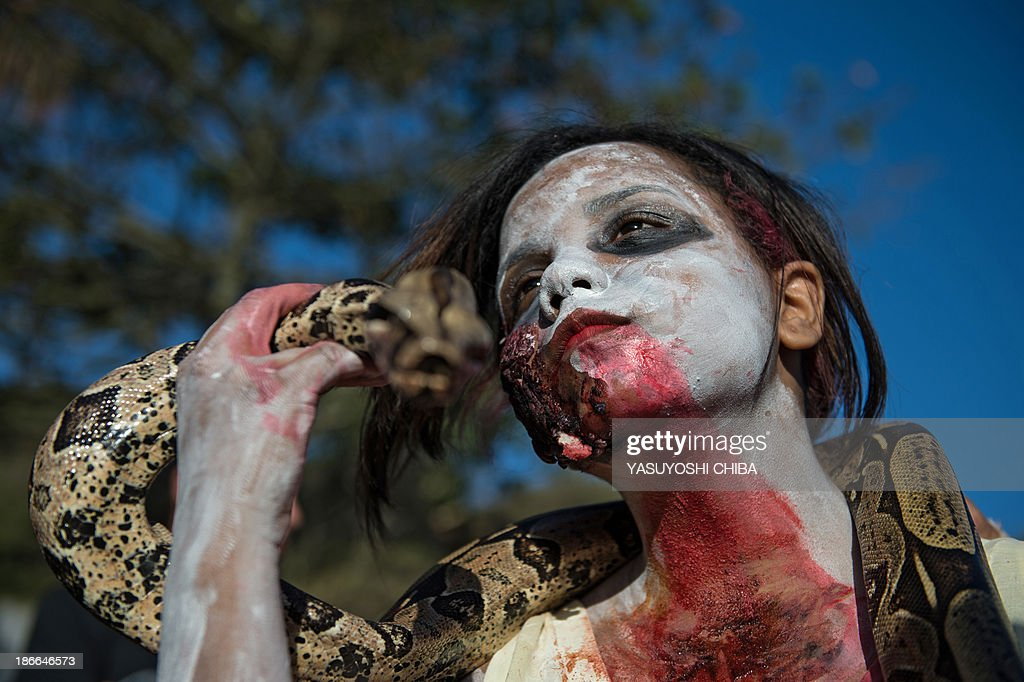 A woman holds a snake after taking part in the Zombie Walk for the Day of the Dead in Arpoador, Rio de Janeiro, Brazil, on November 2, 2013. AFP PHOTO / YASUYOSHI CHIBA