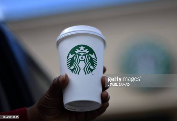 A woman holds a Starbucks coffee cup in Silver Spring Maryland on March 28 2013 The US economy grew more strongly than initially thought in the...