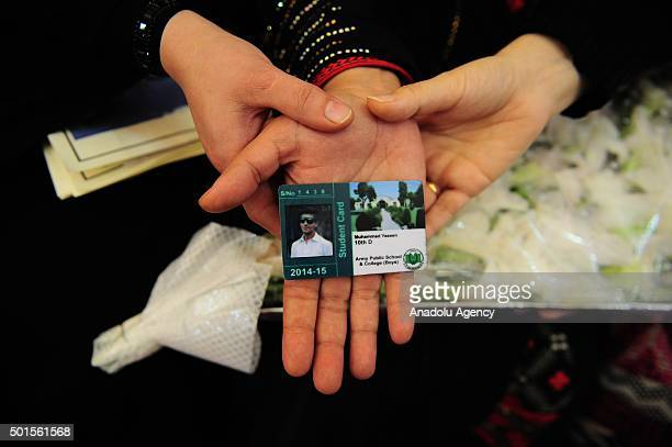 A woman holds a student card of a boy one of the students of Army Public School killed by Taliban militants as they participate the memorial day for...