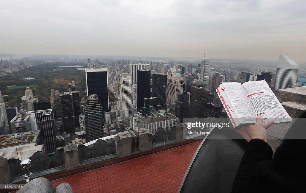 A woman holds a tourist guide book as Manhattan and Central Park are seen from the 'Top of the Rock' observation deck at Rockefeller Center on...