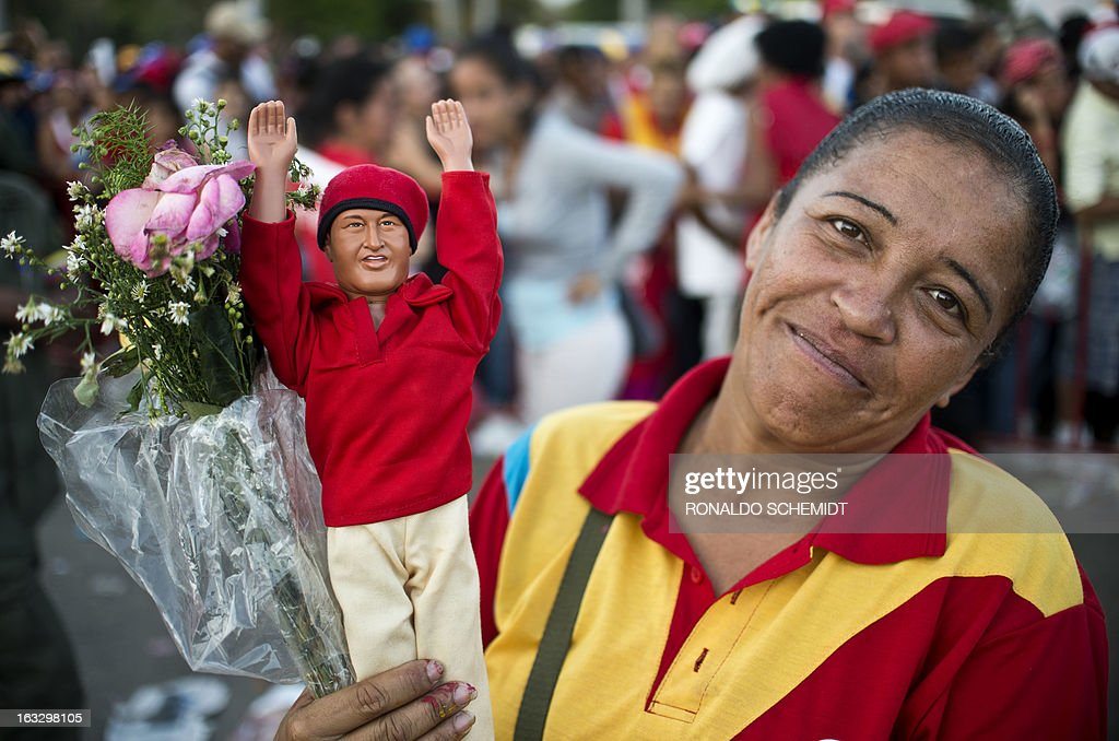 A woman holds a toy representing late Venezuelan President Hugo Chavez, as she waits to pay him respects outside the Military Academy in Caracas on March 7, 2013. Venezuelans filed past the open casket of late President Hugo Chavez as he lay in state after throngs of weeping loyalists gave the firebrand leftist a rousing farewell on the streets on the eve. AFP PHOTO/Ronaldo Schemidt
