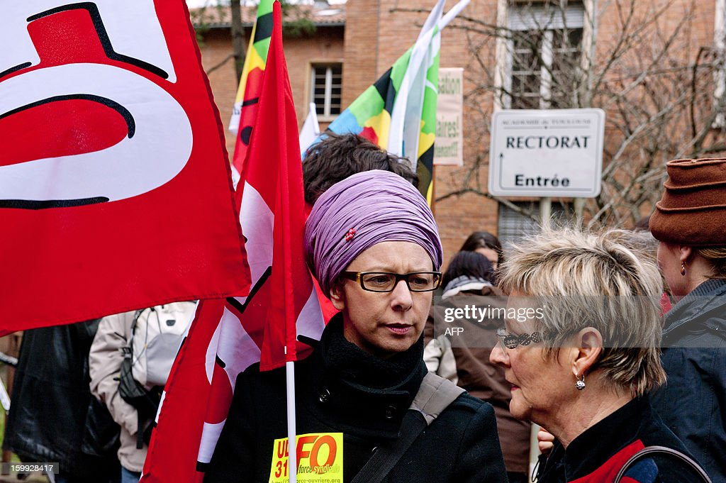 A woman holds a union flag, on January 23, 2013, in front of the headquarters of the local office of the Education department in Toulouse, as she and other teachers take part in a nationwide strike and protest action against a proposed reform to increase the class time of primary school students. The strike and rally was called by French educational trade unions to protest a reform proposition by France's Education Minister, planned for the 2013-2014 schoolyear, which foresees an increase of class time in primary schools to 4.5 days a week and would affect both students and teachers.
