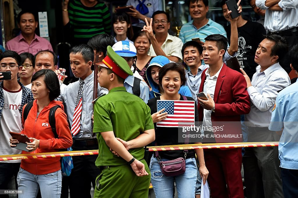 A woman holds a US flag as people line up the streets to catch a glimpse of US President Barack Obama on his way to the airport at the end of two-day visit to Ho Chi Minh City on May 25, 2016. Obama fielded questions on May 25 on everything from rap and weed smoking to leadership and his good looks at a lively town hall-style meeting with young Vietnamese, who say the US leader is a far cry from their staid Communist rulers. / AFP / CHRISTOPHE