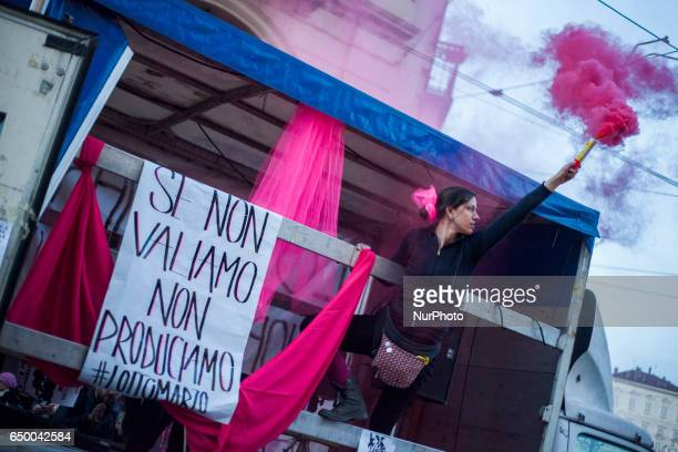 A woman holds a violet smoke bomb during a rally as part of a nationwide 'Lotto Marzo' protest on the International Women's Day 2017 in Torino Italy...